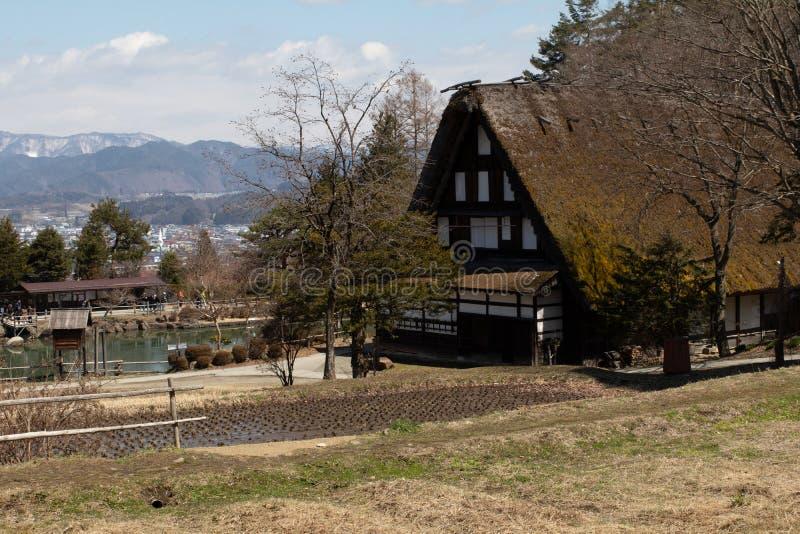Sceniskt landskapfotografi för tidig vår av ett traditionellt hus för halmtäckt tak i lantliga Japan bredvid en risfält arkivfoton