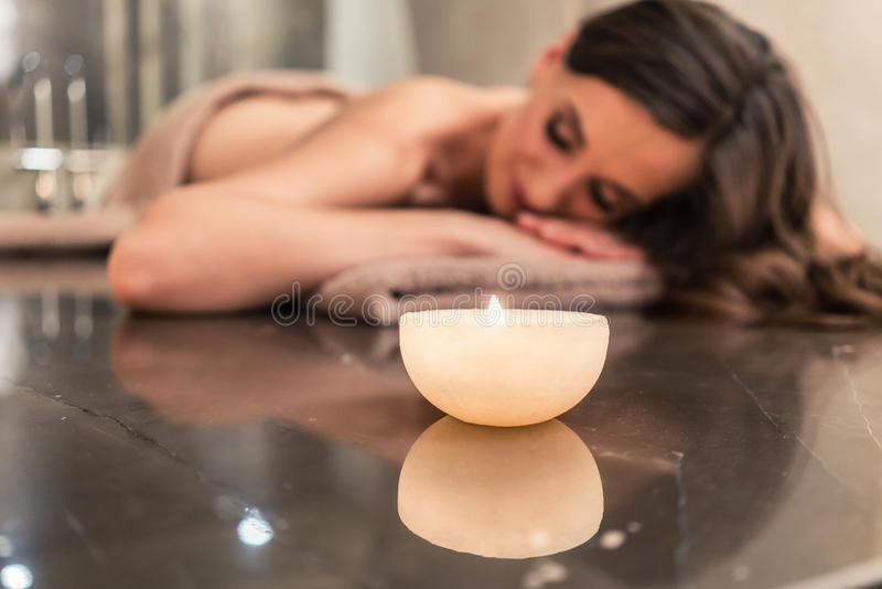 Scented candle next to young woman on marble massage table at sp royalty free stock images