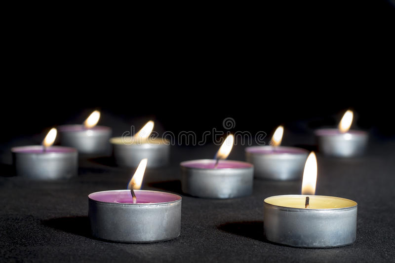 Scented candles of different fragrances, on black. Scented candles of different fragrances, with metal base, on black background stock image
