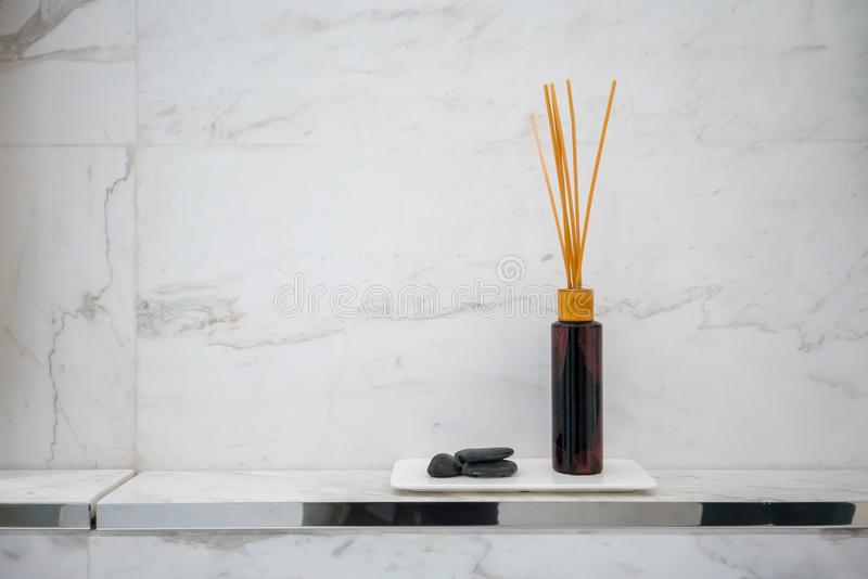 Scented diffuser stick in black glass bottle against white marble wall background. For decoration in luxury bathroom stock photography