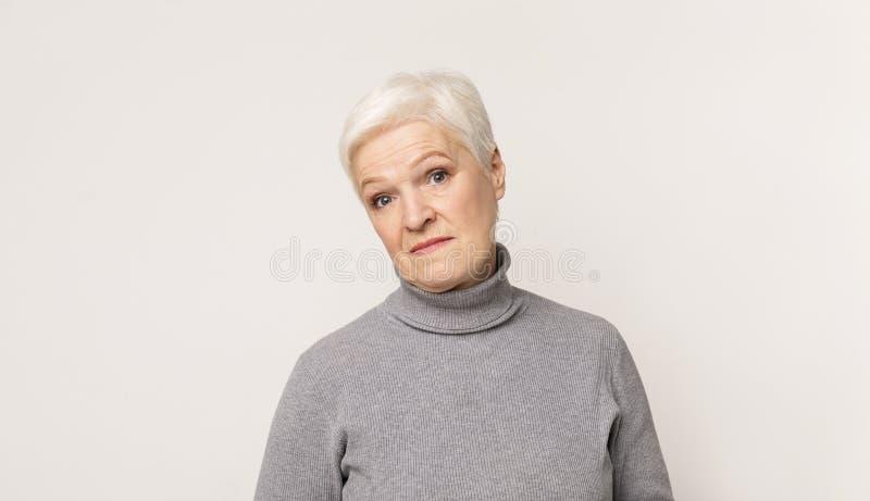 Sceprical senior woman over light stidio background royalty free stock image