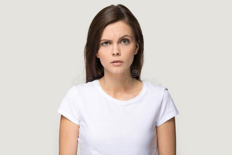 Sceptic suspicious millennial woman pose on grey studio background stock images