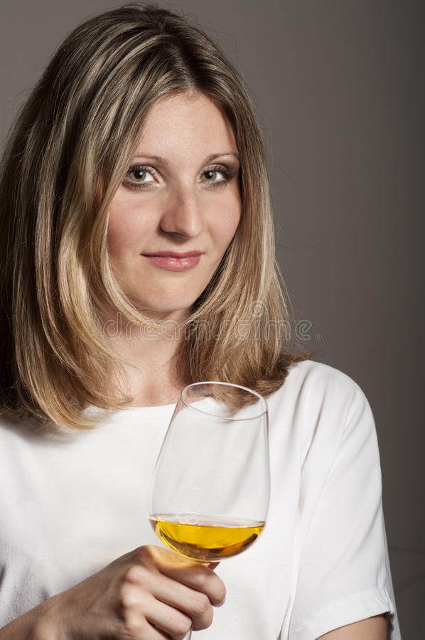 Sceptic woman tastes white wine royalty free stock photos