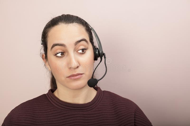 Sceptical help desk operator listening to a call stock image