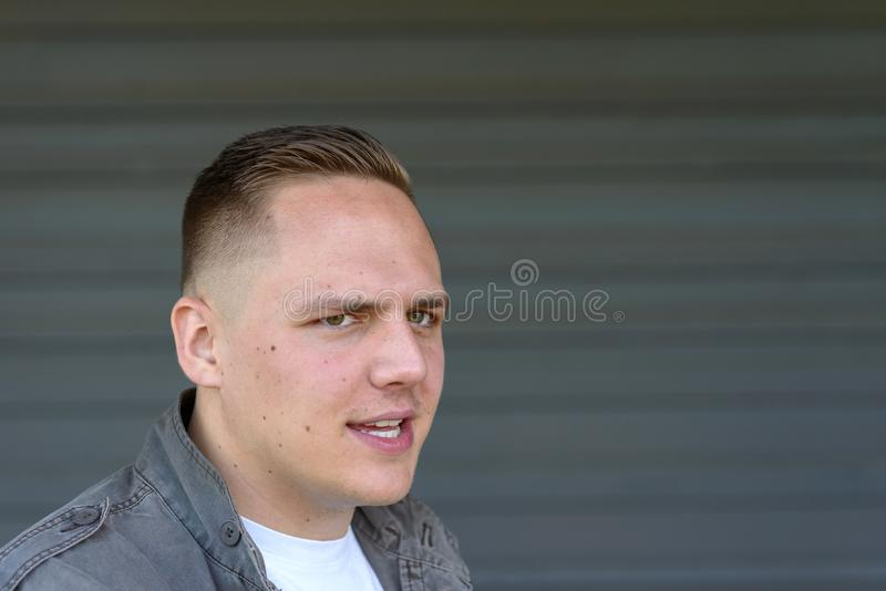 Sceptical man looking aside with a dubious frown. Sceptical young man looking aside at the camera with a dubious frown, intense look and lips parted as though stock photo