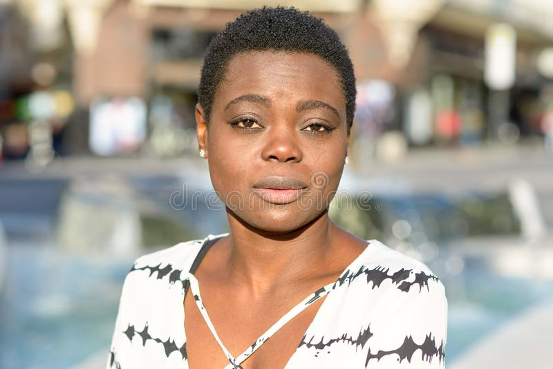 Sceptical young African woman looking at camera. With raised eyebrows and a bored disbelieving look outdoors in town royalty free stock photos