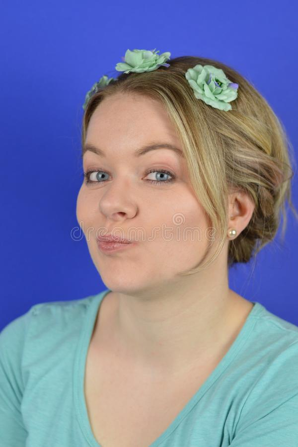 Sceptical young blond woman with flowers on a hair circlet stock images