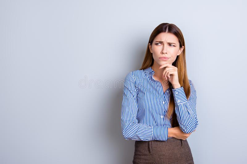 Sceptical young business lady is unsure what to do. She has focused grimace, wearing strict formal wear, standing on pure light b royalty free stock image