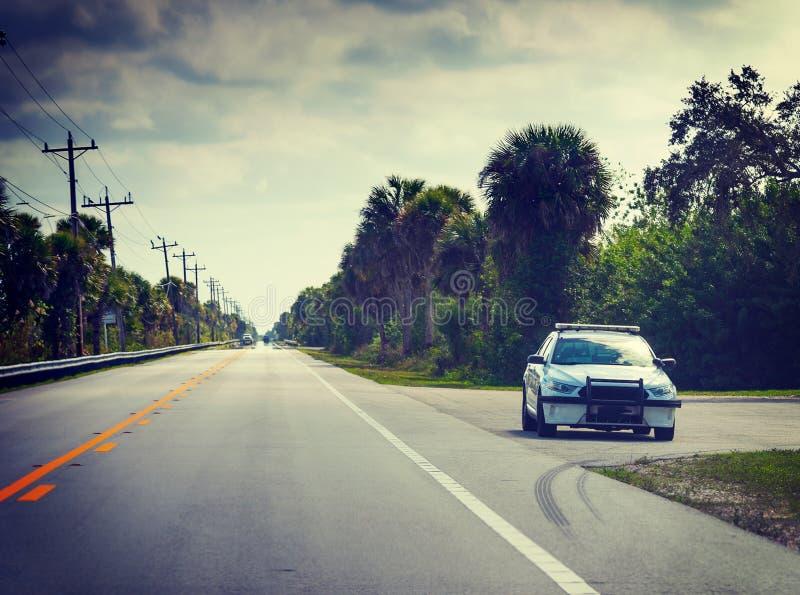 Sceriffo in Florida Everglades ha parcheggiato sul bordo della strada in una giornata nuvolosa immagini stock