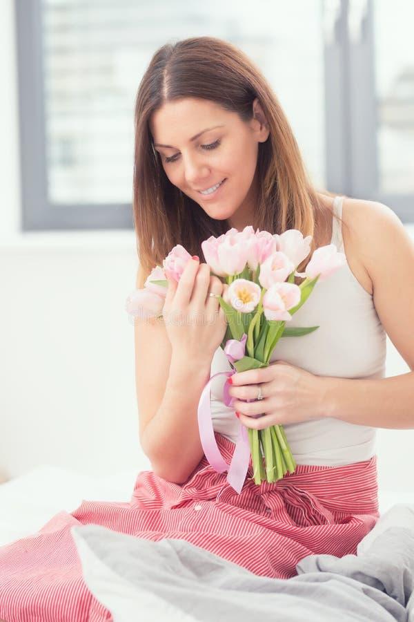 Schöne attraktive Frau, die auf dem Bett zart hält in den Händen einen Blumenstrauß von Frühlingstulpen sitzt stockbilder
