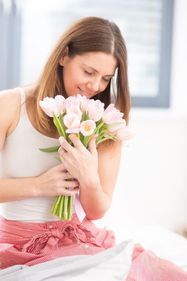 Schöne attraktive Frau, die auf dem Bett zart hält in den Händen einen Blumenstrauß von Frühlingstulpen sitzt lizenzfreies stockfoto