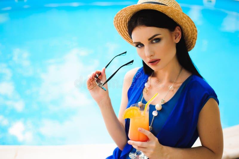 Schöne brunette Frau, die einen blauen Bikini, das Pool genießend, Sommerzeit trägt stockfoto