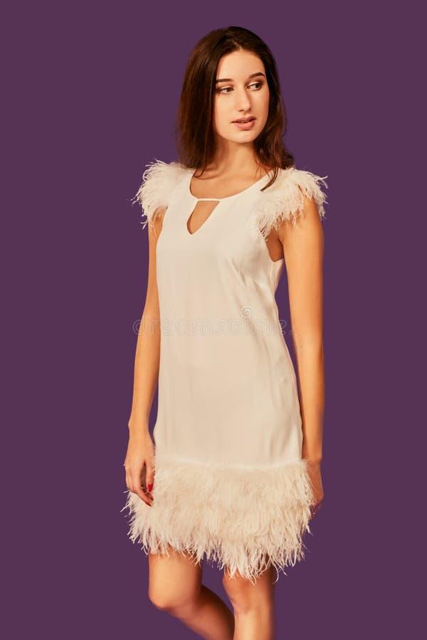 Schöne brunette Frau im weißen Kleid des eleganten Cocktails wirft im Studio auf purpurrotem Hintergrund auf T stockfotografie
