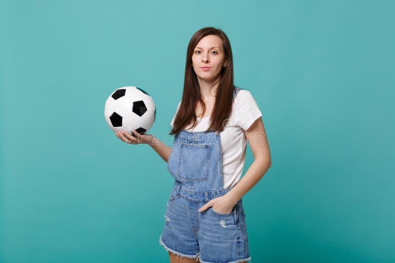 Schöne Fußballfanstützlieblingsteam der jungen Frau, das Fußball lokalisiert auf blauem Türkiswandhintergrund hält lizenzfreie stockfotografie