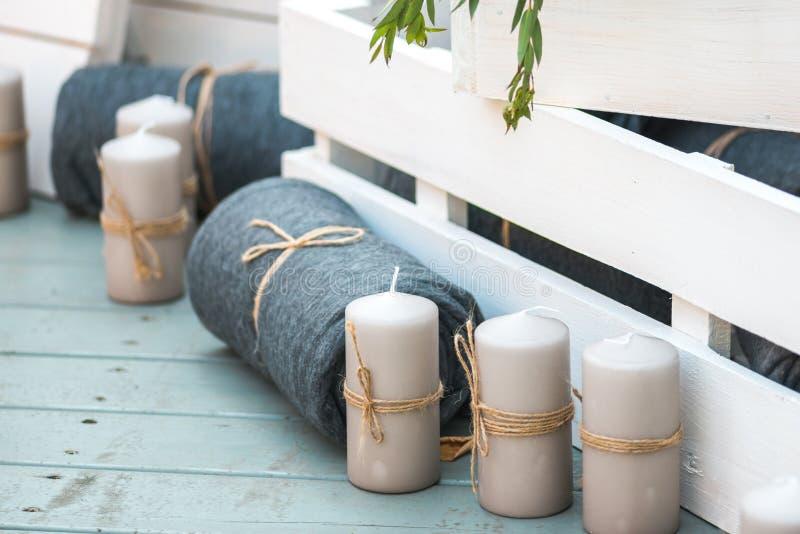 Schöne gefaltete Decken und dekorative weiße Kerzen gegen weiße gemalte hölzerne Kisten aller es steht auf dem Blau lizenzfreie stockfotos