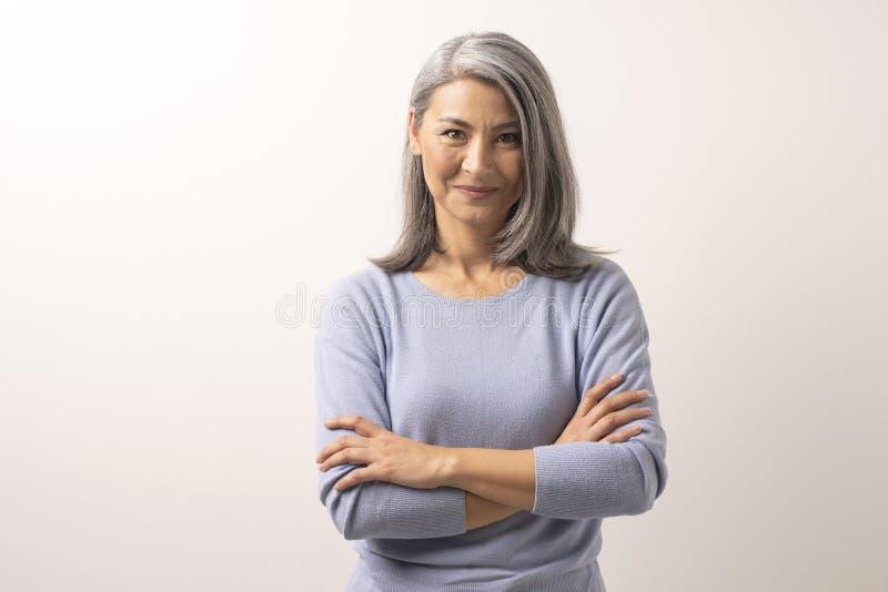 Schöne grau-haarige Frau mit den gekreuzten Armen lizenzfreies stockbild