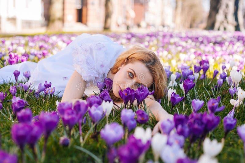 Schöne junge Blondine mit dem blauen Augen- und weißemkleid, das auf dem Teppich unter den Frühlingsblumenkrokussen liegt lizenzfreie stockfotos