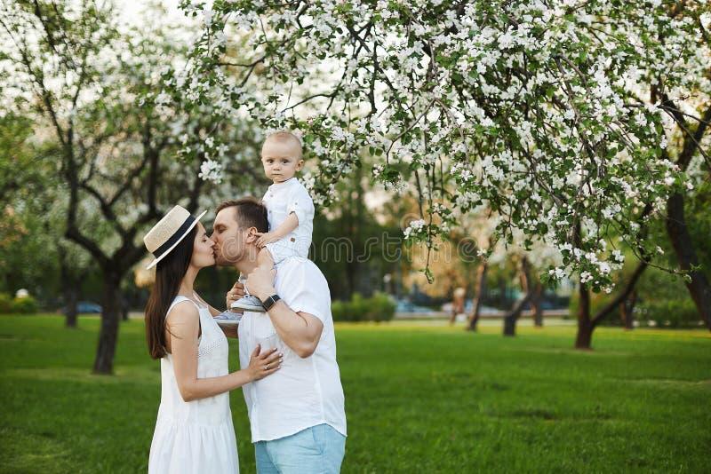 Schöne junge Eltern und ihr netter kleiner Sohn haben Spaß am grünen Park stockbild