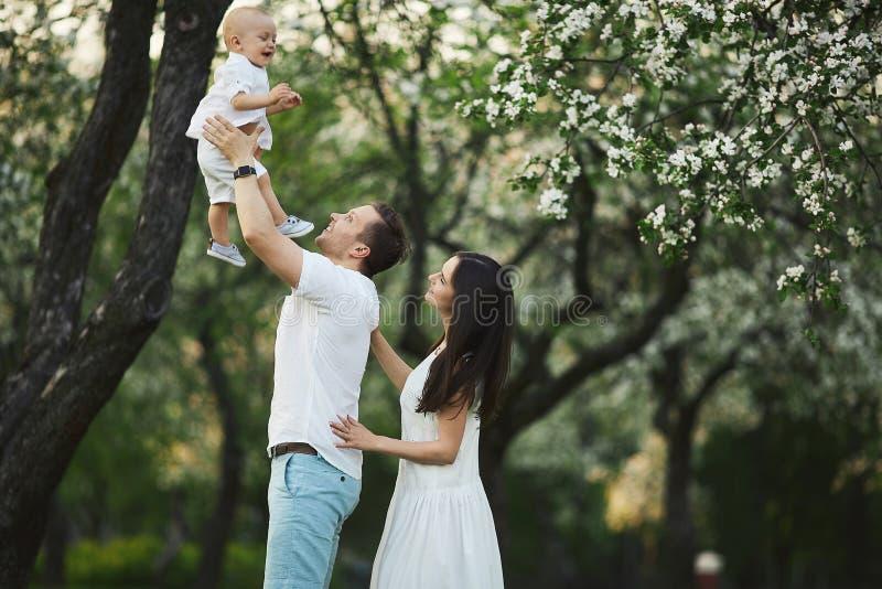 Schöne junge Eltern und ihr netter kleiner Sohn haben Spaß am grünen Park stockfotos