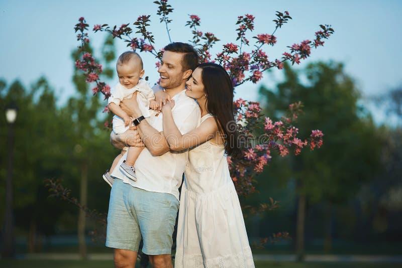 Schöne junge Eltern und ihr netter kleiner Sohn haben Spaß am grünen Park lizenzfreie stockfotografie