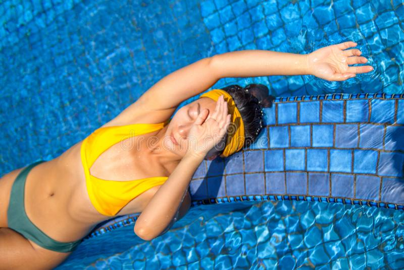 Schöne junge Frau, die am Swimmingpool sich entspannt stockfotos