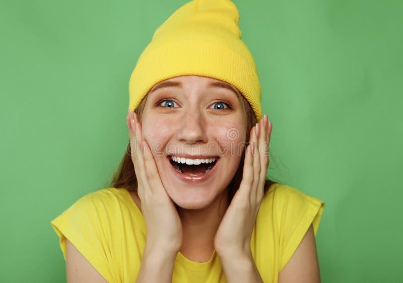 Schöne junge Frau, die zur Kamera über grünem Hintergrund lächelt lizenzfreies stockfoto