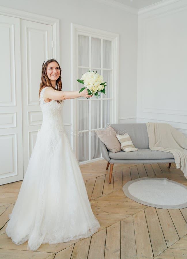 Schöne lächelnde brunette Frauenbraut im Hochzeitskleid mit klassischem Blumenstrauß der weißen Rosen, Ganzaufnahme stockfotografie