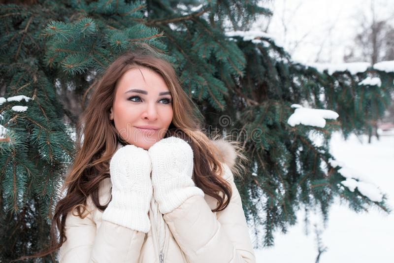 Schönes brunette Mädchen im Winterpark auf dem Hintergrund von grünen Bäumen im Weiß hinunter Jacke mit dem langen Haar, glücklic lizenzfreie stockbilder