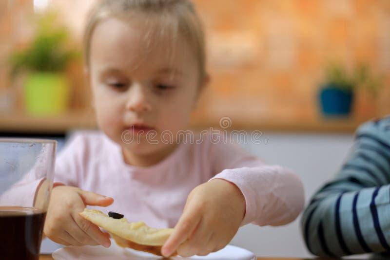 Schönes glückliches nettes Baby, das Scheibe der selbst gemachten Pizza isst stockfoto