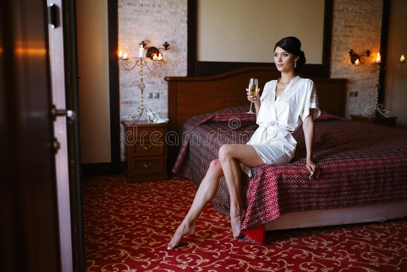 Schönes Mädchen in einem weißen Mantel auf dem Bett mit einem Glas Champagner stockbilder