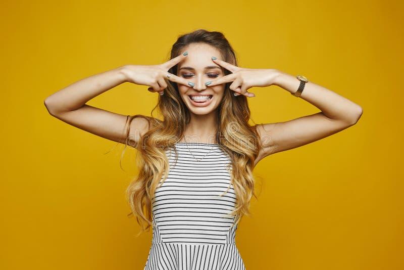 Schönes und modernes blondes vorbildliches Mädchen mit einem reizend Lächeln im weißen gestreiften Kleid hat einen Spaß und die A stockfotos