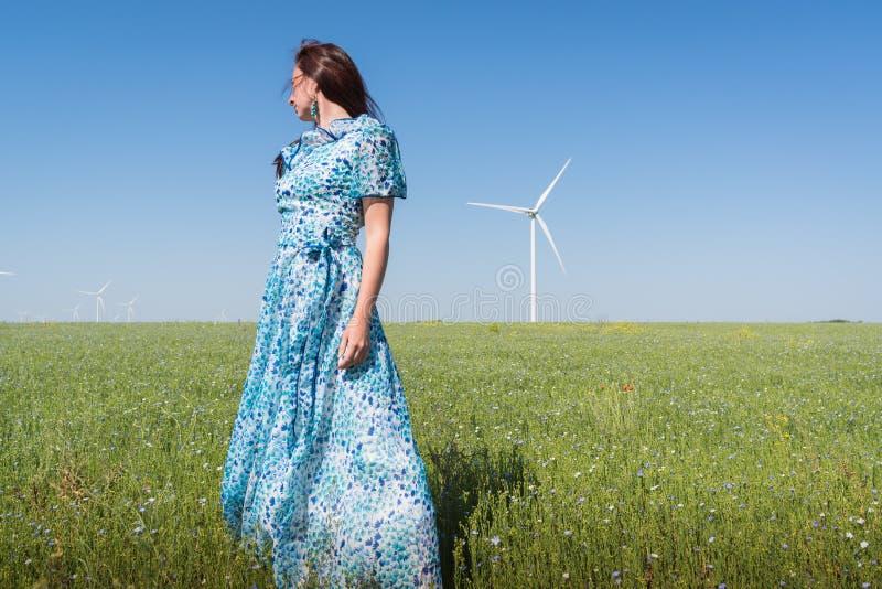Schönheit im blauen Kleid auf grünem Feld mit Windgeneratorturbinen und Hintergrund des blauen Himmels stockfoto