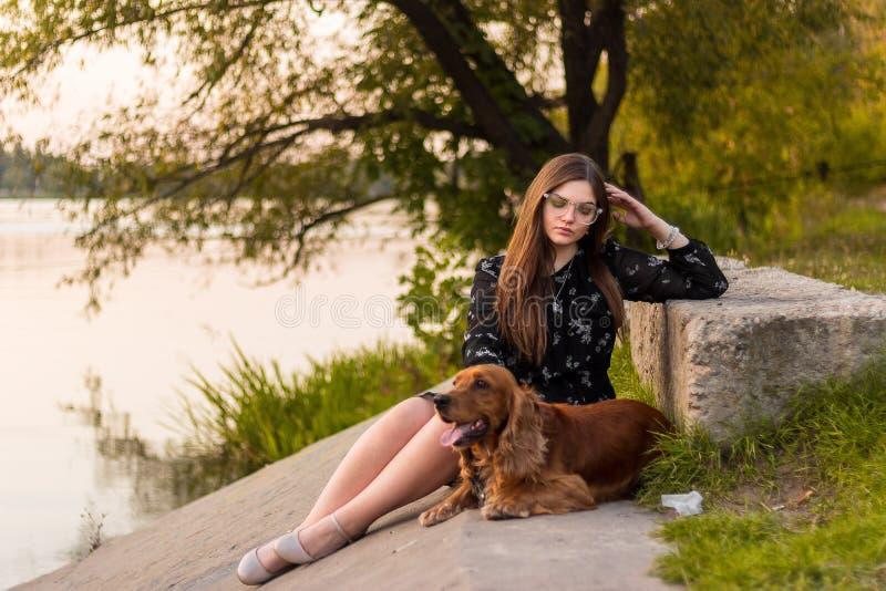 Schönheitsfrau mit ihrem Hund, der draußen spielt stockbild