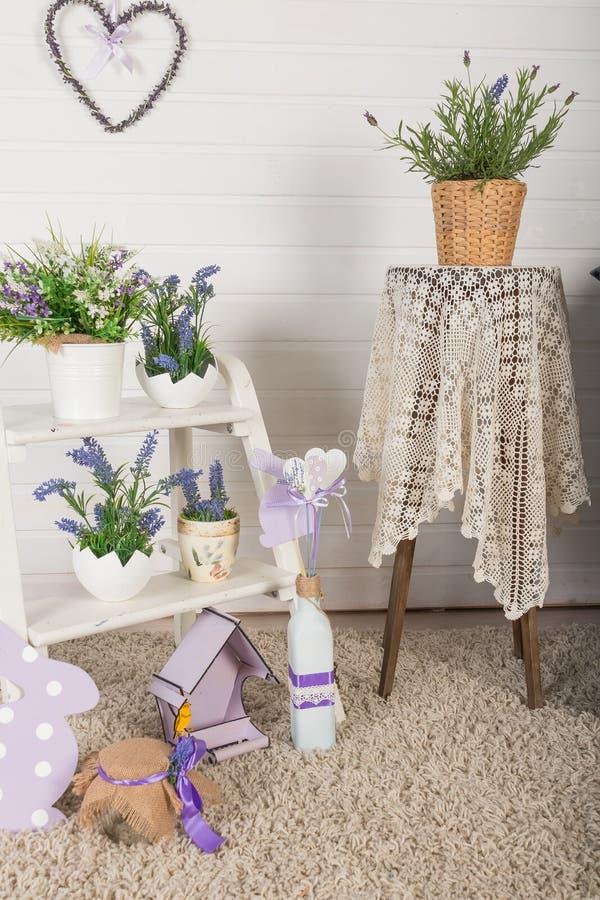Schäbiger schicker Innendekor für Bauernhaus Lavende, Anlage und Weinlesetabelle, Regal über Pastellwand Provence-Haus stockbilder