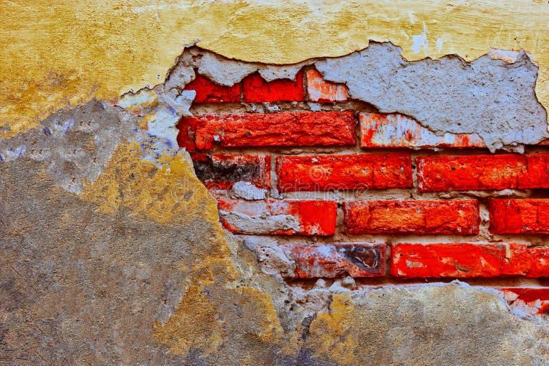 Schädigende Backsteinmauer mit abgenutztem Gips lizenzfreies stockfoto
