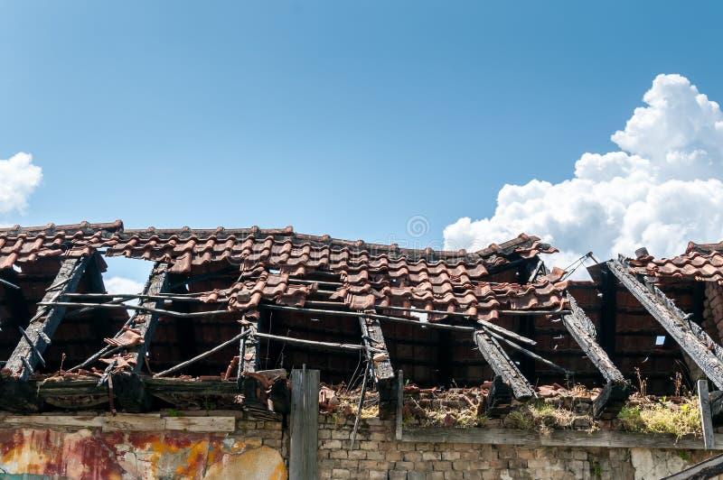 Schädigendes und gebrochenes eingestürztes Dach des verlassenen Hauses nach Feuer von der Granatenbombe mit Fliesen und Hintergru stockfotos
