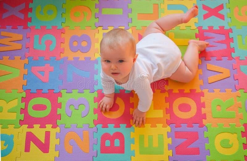 Schätzchen auf Alphabetmatte stockfotografie