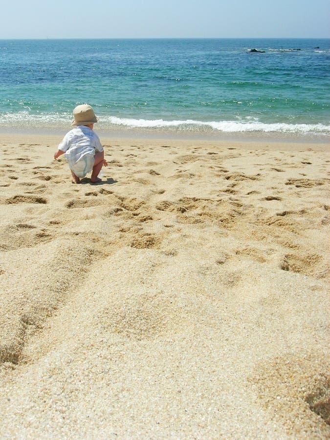 Schätzchen, das auf dem Strand spielt stockfoto