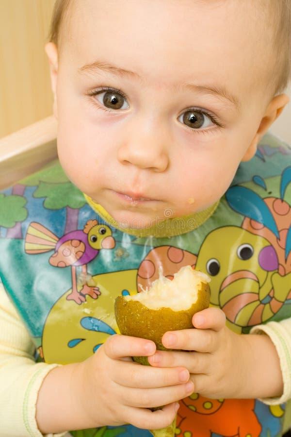 Schätzchen, das eine Birne isst lizenzfreie stockbilder