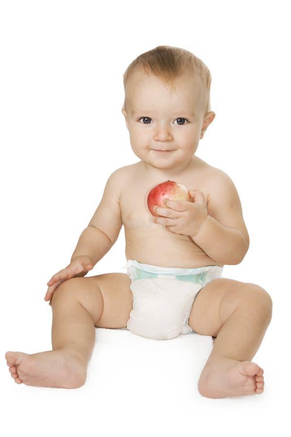 Schätzchen, das einen Apfel anhält. stockbilder