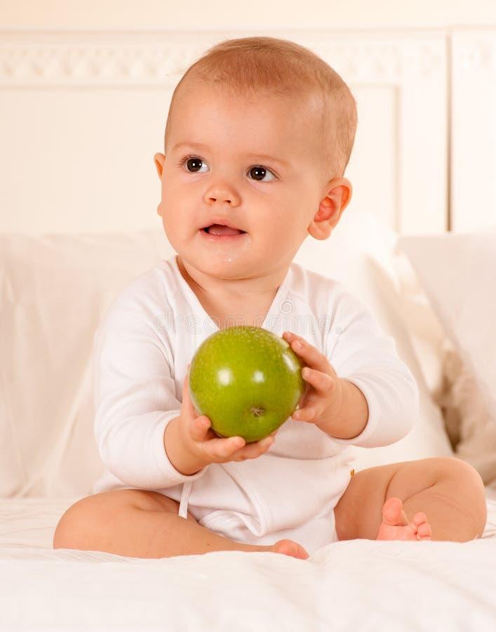 Schätzchen, das grünen Apfel manipuliert lizenzfreie stockfotos