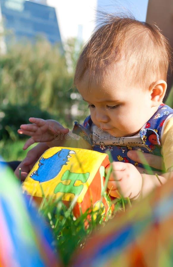 Schätzchen, das im Gras liegt und mit Blöcken spielt stockfotos