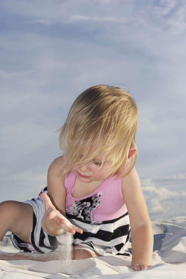 Schätzchen, das im weißen Sand spielt stockfotografie