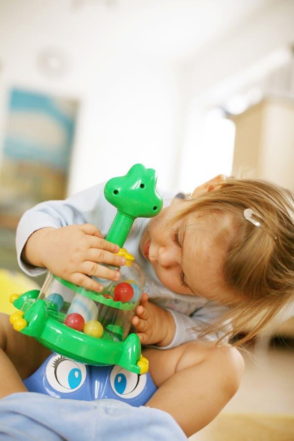 Schätzchen, das mit Spielwaren spielt stockbild