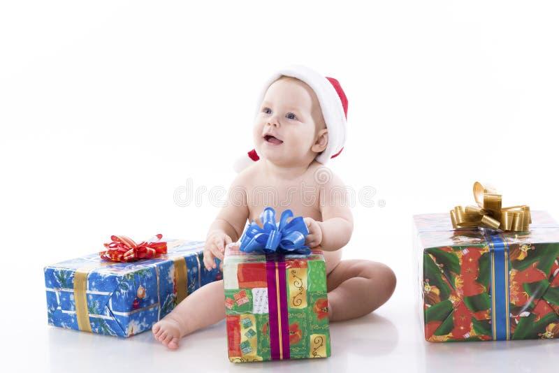 Schätzchen in einer Schutzkappe von Weihnachtsmann mit Geschenken stockfotos