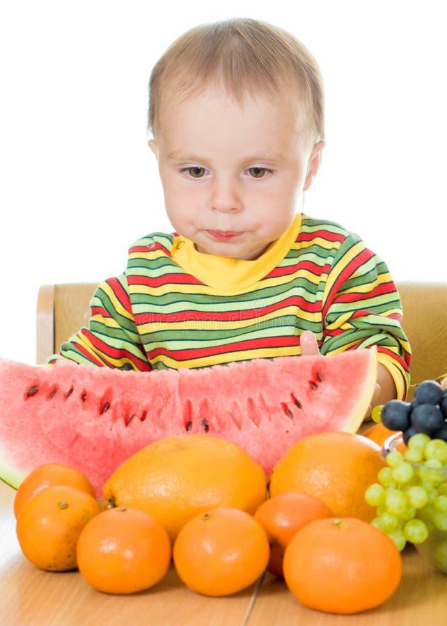 Schätzchen isst Frucht auf einem weißen Hintergrund stockfotografie