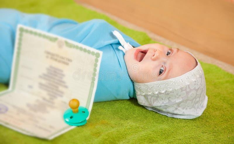 Schätzchen mit Bescheinigung der Geburt stockfotografie