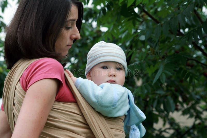 Schätzchen mit Mamma im Riemen stockbilder