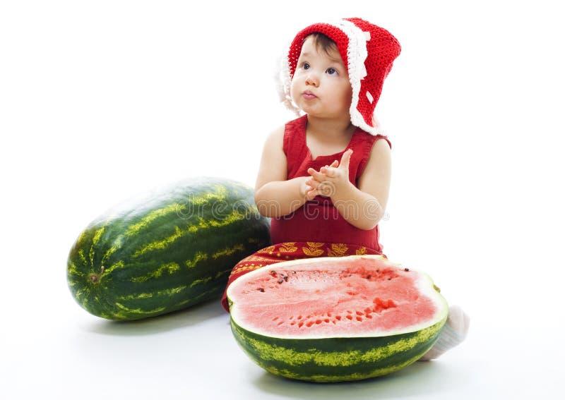 Schätzchen mit rotem Kleid und Schutzkappe sitzen mit Wassermelone stockbilder