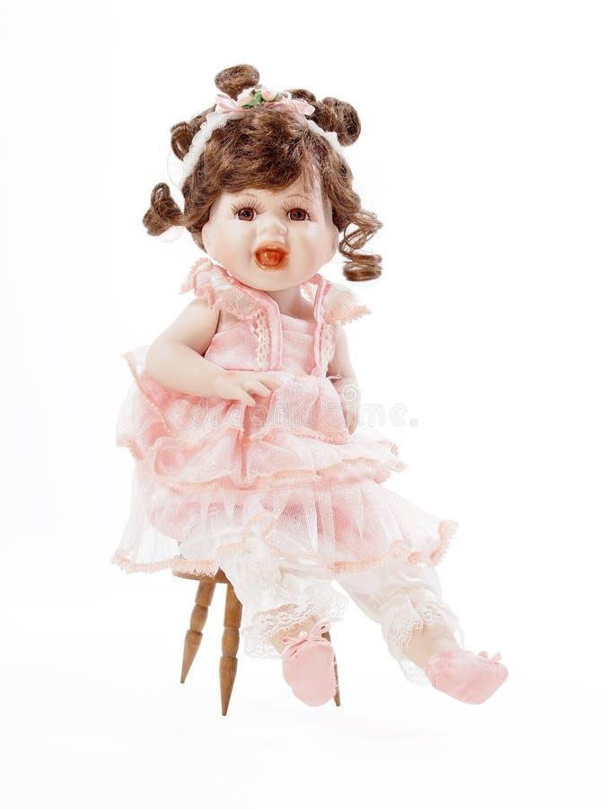 Schätzchen-Porzellan-Puppe, die auf einem hölzernen Stuhl sitzt lizenzfreie stockfotos